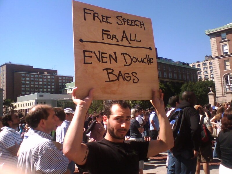 "Man at a protest holding up a sign that reads: ""Free speech for all - even douche bags"""